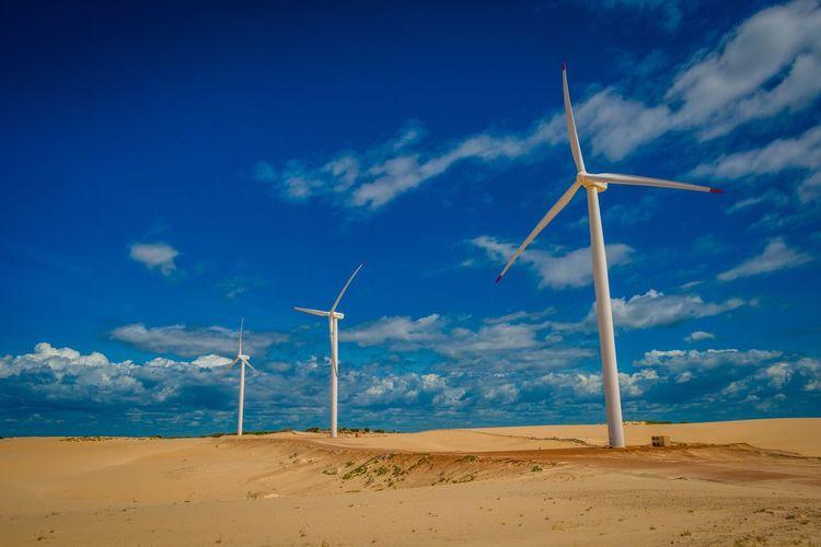 Windmills in desert against sky