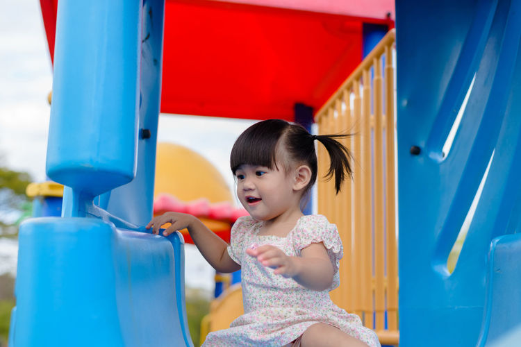 Cute girl enjoying at jungle gym in playground