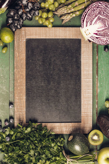 High angle view of vegetables and fruits with blackboard on table