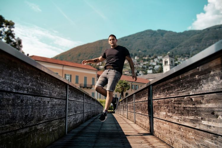 Full length of young man jumping on mountain in city against sky