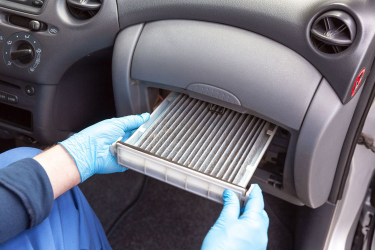 Midsection of man repairing air conditioner in car