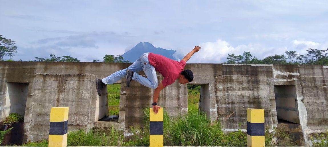 Man balancing on bollard against wall