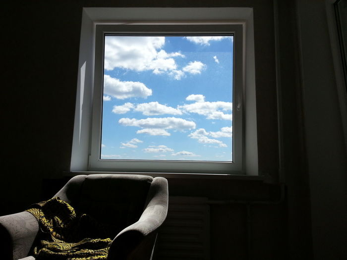 View Of Blue Sky And Clouds Seen Through Window