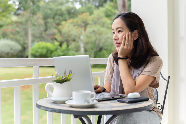 Woman holding coffee while sitting on table