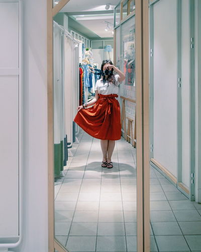 Full length of woman photographing while reflecting on mirror in store