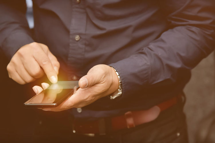 Midsection of man holding mobile phone