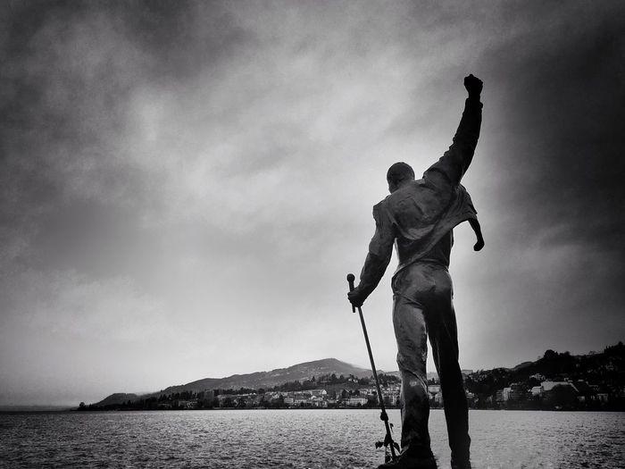 Human statue in lake geneva against cloudy sky