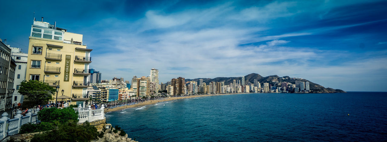 Panoramic View Of Sea And Buildings Against Sky