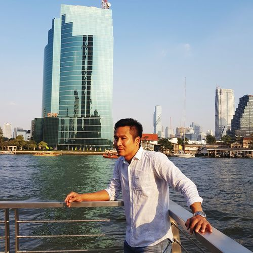 Young man standing by railing against river and buildings