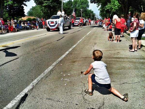 Boy picking up candy at a parade Color Eye4photography  Color Photography EyeEmbestshots Forth Of July July 4th July4th Childhood Parades Parade Time Parade Summertime Summer Childhood Memories Americana America Colors Child Boy Children Photography Kids Having Fun Kids Being Kids Having Fun Kids Son