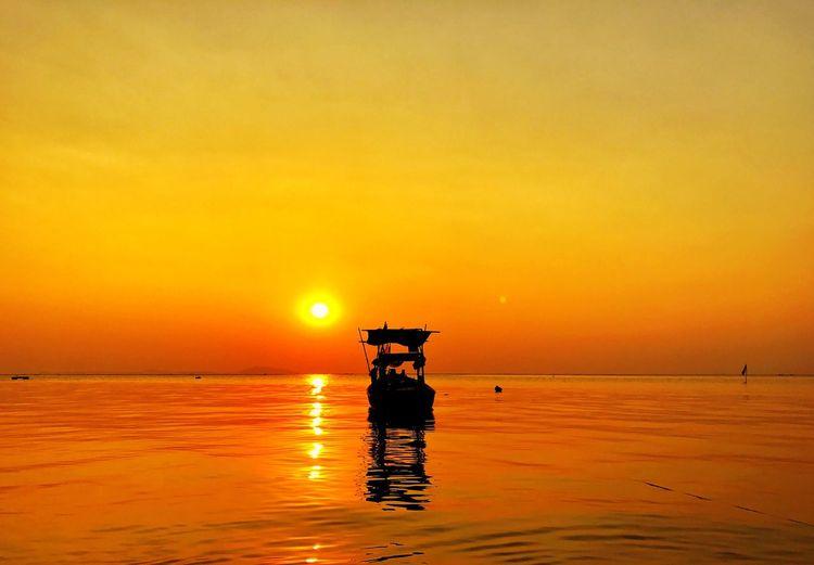 Silhouette boat sailing in sea against orange sky