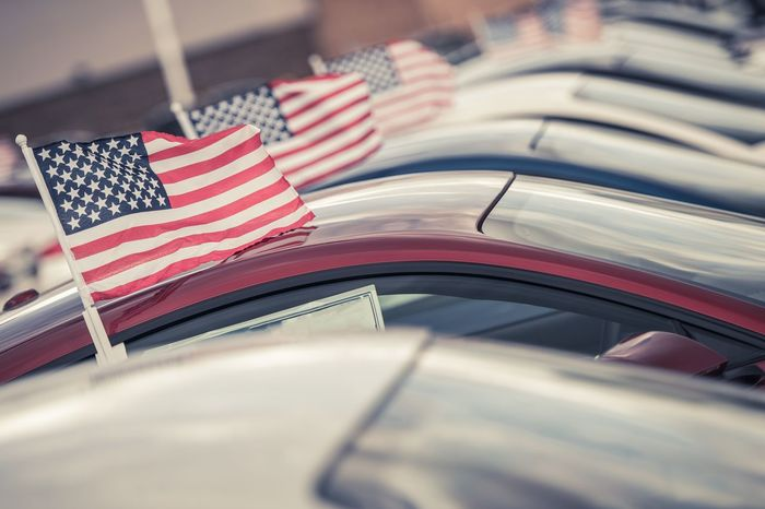 American Made Cars Sale Concept Photo. United States Economy and Market Theme. Brand New Vehicles For Sale with American Flags Attached. Dealership Lot. American Made Proud Auto Automotive Car Car Sales Close-up Day Dealer Dealership Flag Flags In A Row No People Outdoors Patriotism Selling Stars And Stripes