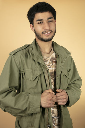 Beard Beige Background Button Down Shirt Casual Clothing Clothing Colored Background Confidence  Front View Fully Unbuttoned Government Handsome Indoors  Looking At Camera One Person Portrait Smiling Standing Studio Shot Uniform Waist Up Young Adult Young Men
