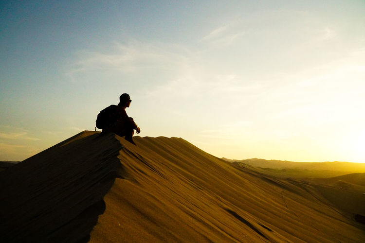 Silhouette man sitting on sand against sky during sunset