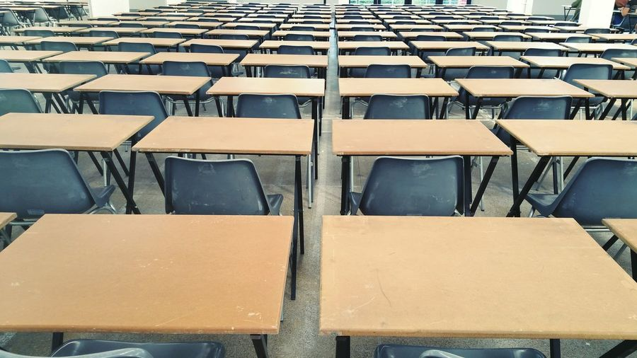 Empty Chairs And Tables Arranged In Classroom