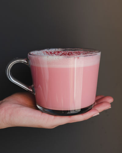 Human Hand Human Body Part Food And Drink Refreshment Drink Hand Glass Holding One Person Drinking Glass Healthy Eating Food Freshness Smoothie Indoors  Dairy Product Lifestyles Close-up Household Equipment Milk Pink Color Body Part Finger Black Background Latte Grey Color