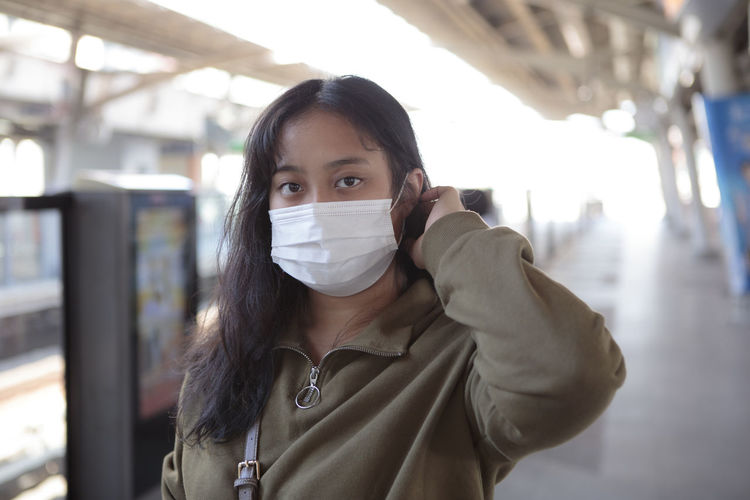 Portrait of beautiful young woman wearing mask on railroad station platform