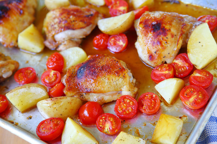 Chicken thigh dinner with tomatoes and potatoes Home Cooking Natural Light Poultry Textures Balanced Meal Cherry Tomatoes Chicken Thighs Close-up Delicious Food Freshness Healthy Eating Indoors  No People One Pan Meal Overhead Potatoe Ready-to-eat Red Roast Chicken Sheet Pan Dinner Studio Shot Tasty