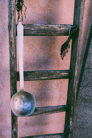 An antique ladle resting on an old ladder in a rustic scene. Ancient Antique Architecture Close-up Country House Indoors  Inside Photography Ladle No People Old Vintage Wood - Material Wooden Stairs