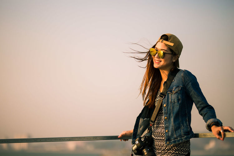 Young woman in sunglasses standing against sky