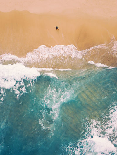 Aerial view of a lone man walking on a sandy beach full of waves