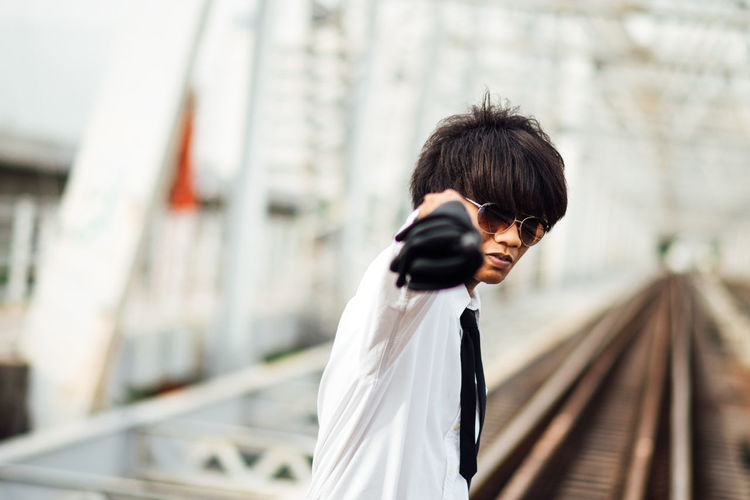 Portrait of young man gesturing while standing on railroad track