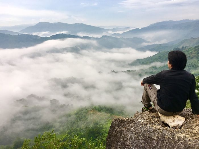 Full length of hiker sitting on rock by mountains against cloudy sky