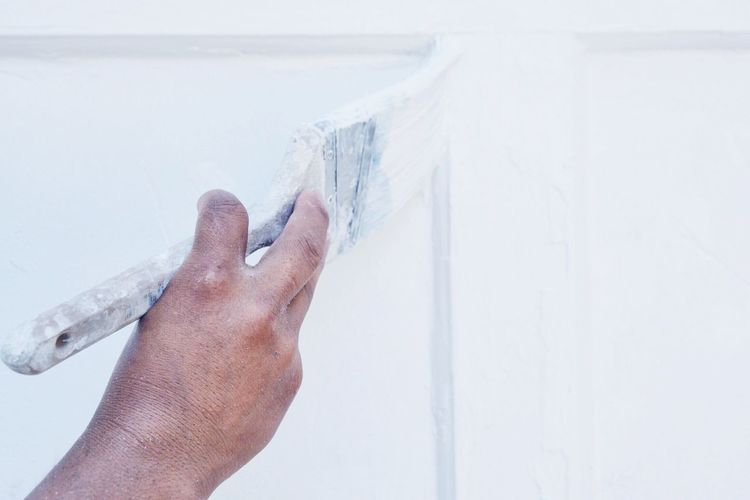 Cropped hand of person painting white wall
