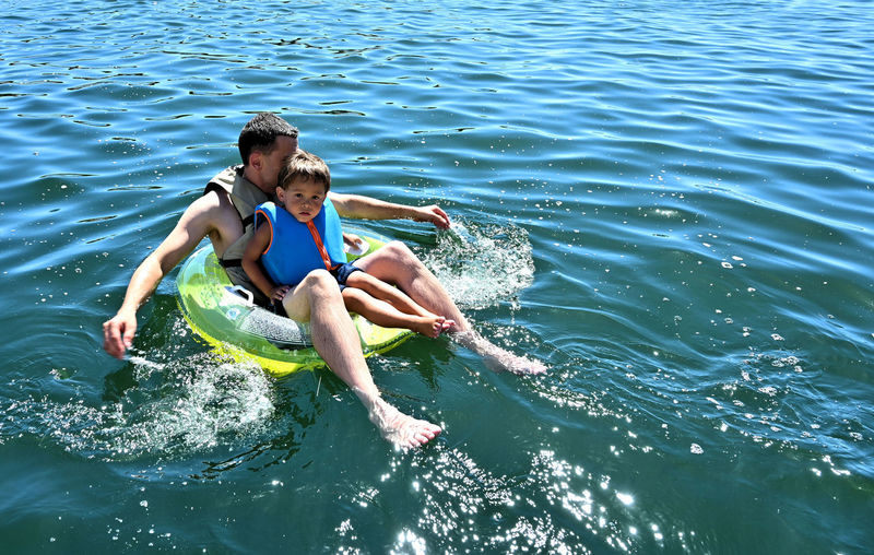 At Don Pedro Lake, CA with Daddy Floating on the inflatable. Water Leisure Activity Lifestyles Real People Two People Men Nature Sea Day Enjoyment Holiday Trip Togetherness Vacations People Sunlight Shirtless Young Adult Outdoors Inflatable