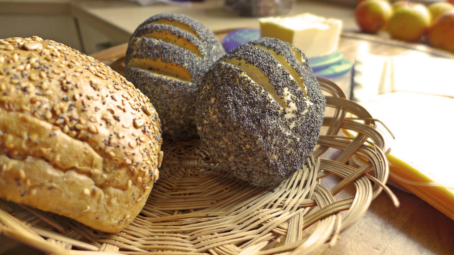 Close-Up Of Breads With Poppy Seeds In Wicker Plate On Table At Home