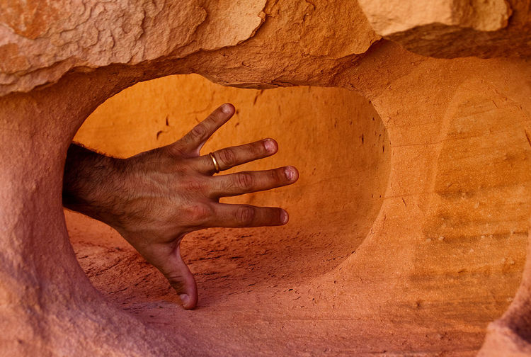 Human hand touching rock formation