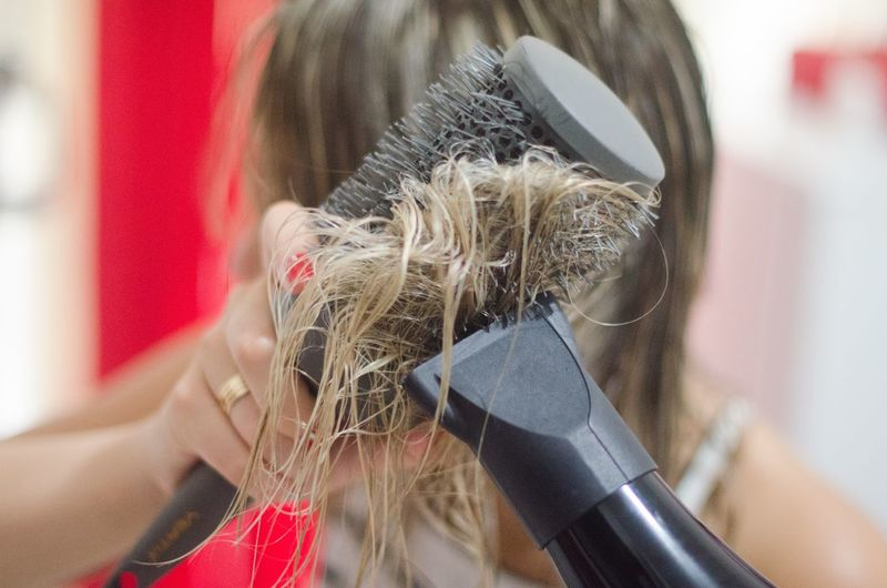 Close-up of woman drying hair with dryer