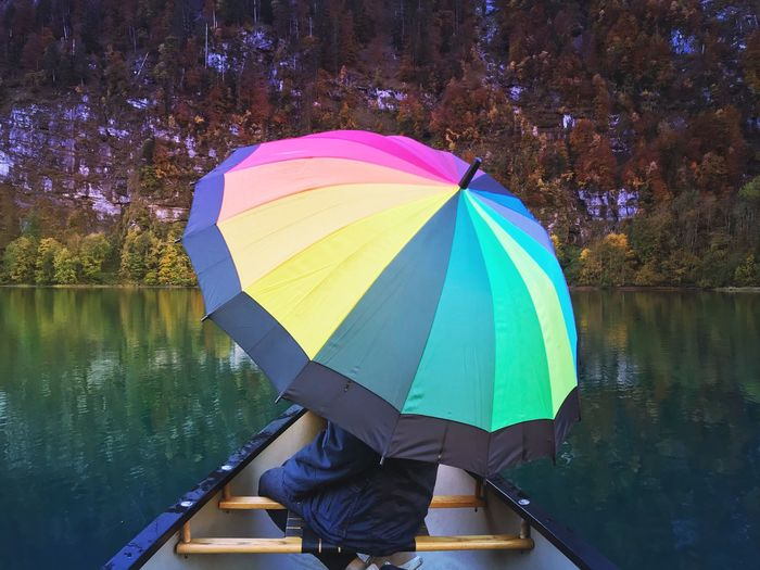 Woman with umbrella standing by lake during rainy season