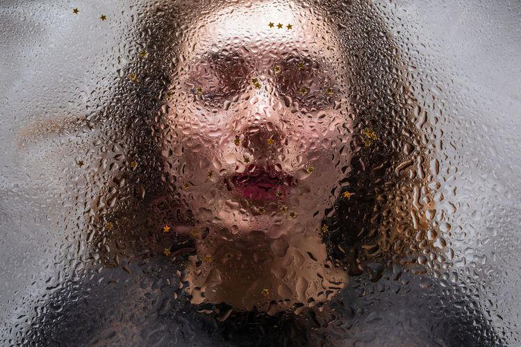 Close-up of woman seen through wet glass