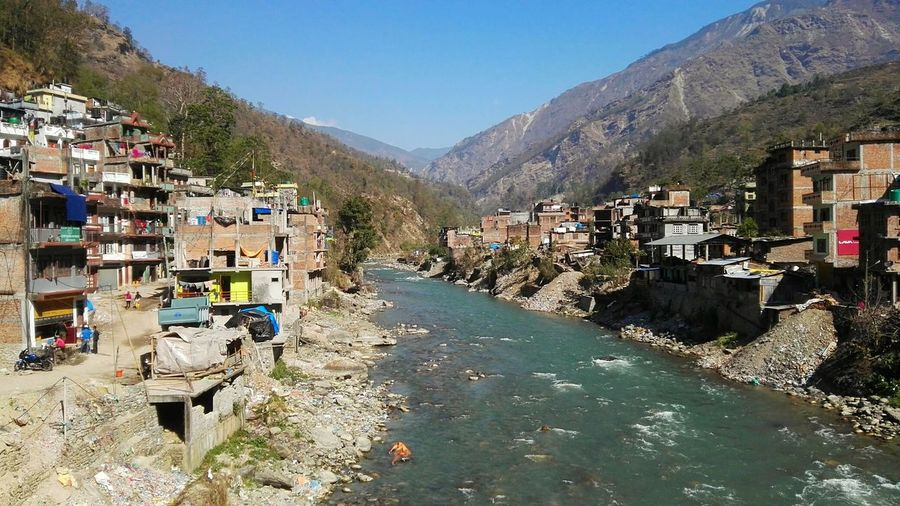 Learn & Shoot: Balancing Elements River Dividing Town Nepal Asia Houses Along River Front Water Mountains In Background