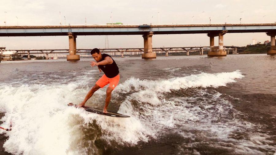 Full length of man wakeboarding in river against bridge