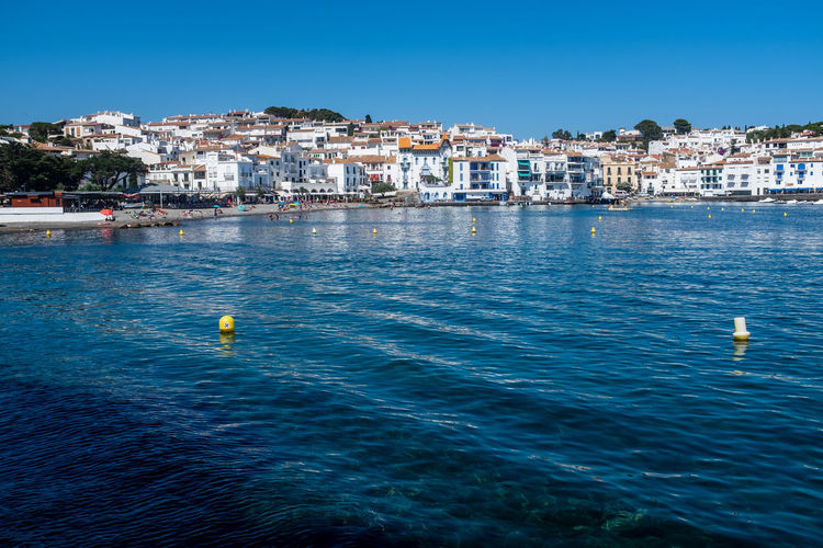 Sea by townscape against clear blue sky. cadaques, spain.