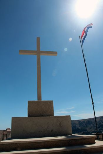 Stone Cross at the graveyard on the mountain high above Baska,Croatia. Baska,Croatia Christianity Croatia Friedhof God Krk  Patriotism Stone Cross Unity Blue Close-up Cross Day Flags In The Wind  Gravestone Graveyard Low Angle View Mahnmal National Flag No People Outdoors Religion Sky Spirituality State And Religion