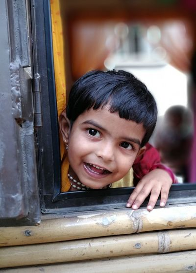 Portrait Of Smiling Girl Looking Through Bus Window