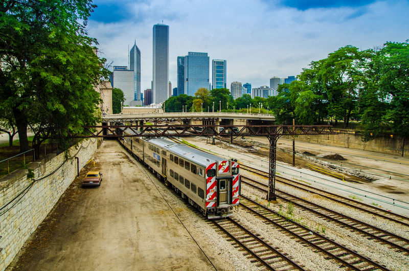 Train moving on railroad tracks in city