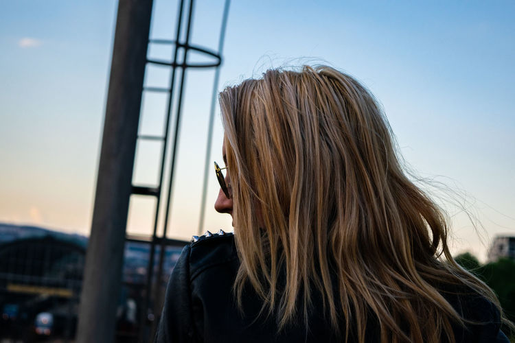 Young woman with blond hair against sky during sunset