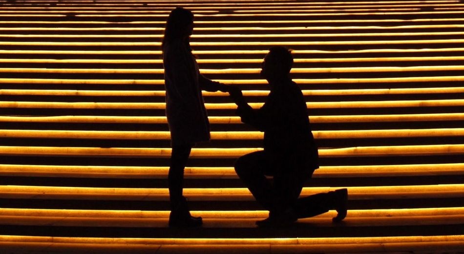 Silhouette man on knee holding woman hand at night