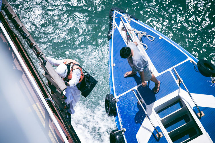 man from cargo ship move down to small boat Adult Adults Only Boat Deck Day High Angle View Leisure Activity Men Nature Nautical Vessel Occupation Only Men Outdoors People Sailing Sea Teamwork Three People Togetherness Water