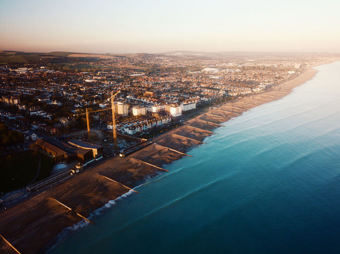 High angle drone view of worthing sea front with city scape and beach at sunset