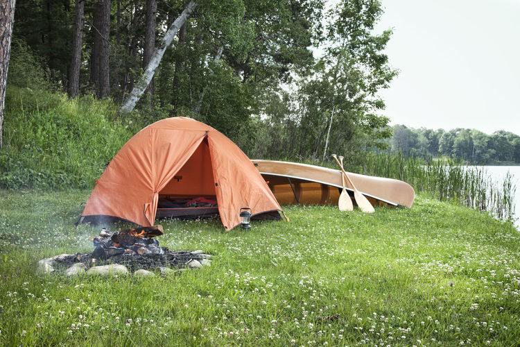 Orange tent and canoe on grass by lake