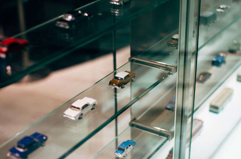 Miniature cars on glass shelf