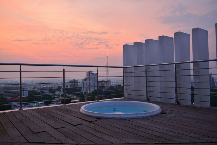 Swimming pool in city against sky during sunset