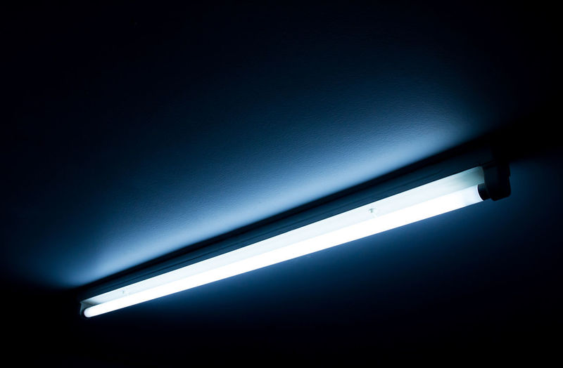 Low angle view of illuminated lights in dark room