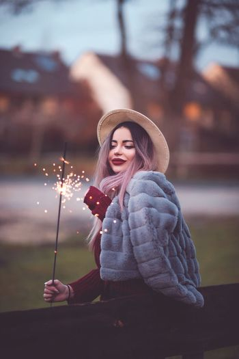 Side view of young woman holding sparkler while standing at park