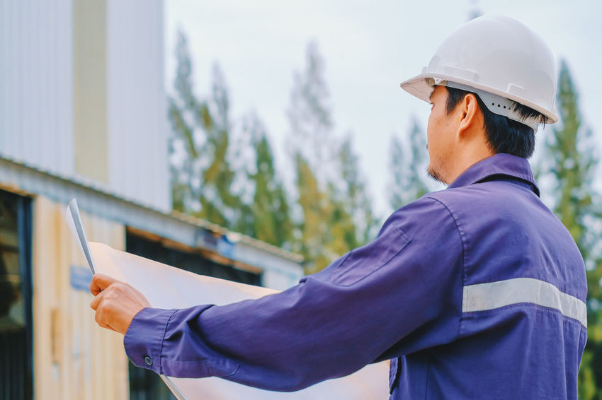 Asian  Construction Employee Industrial Industry Man Plan Standing Uniform Blueprint Building Contractor Engineer Factory Foreman Helmet Holding Inspector Job One Person Outdoors Project Safety Site Supervisor